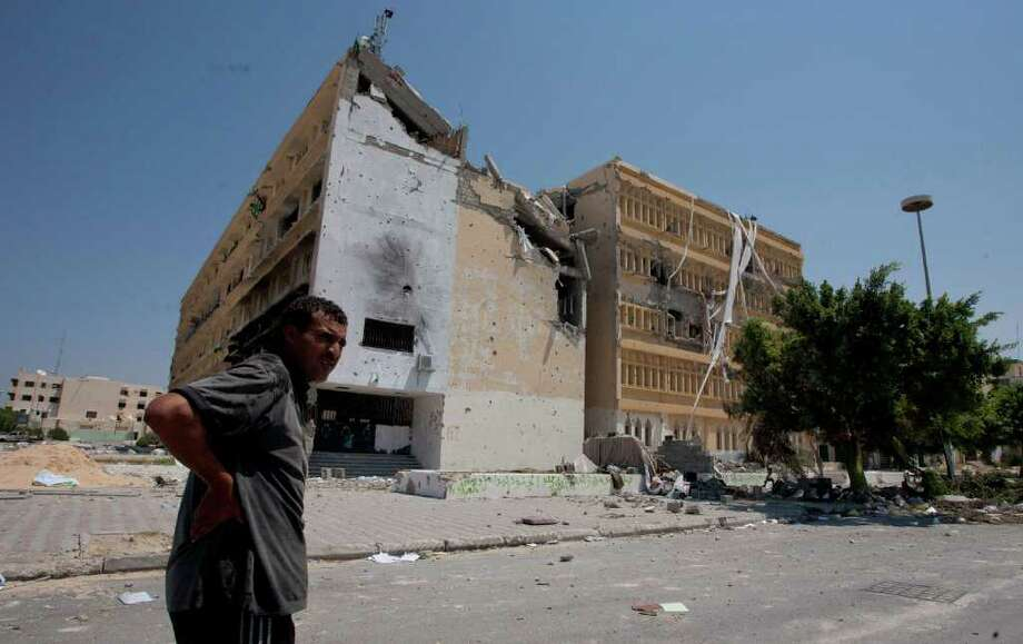 A Libyan man looks on in front of the partially destroyed building at the central square in Zawiya, LIbya, Saturday, Aug. 20, 2011. Libyan rebels expelled government forces from the strategic western city of Zawiya on Saturday, a major victory for the opposition in their march on Moammar Kadafi's stronghold of Tripoli. (AP Photo/Giulio Petrocco) Photo: Giulio Petrocco / AP