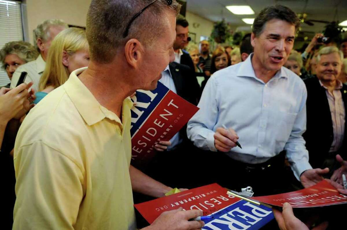 Republican presidential candidate, Texas Gov. Rick Perry, signs autographs for supporters at Tommy's Ham House Saturday, August 20, 2011, in Greenville, S.C. (AP Photo/ Richard Shiro)