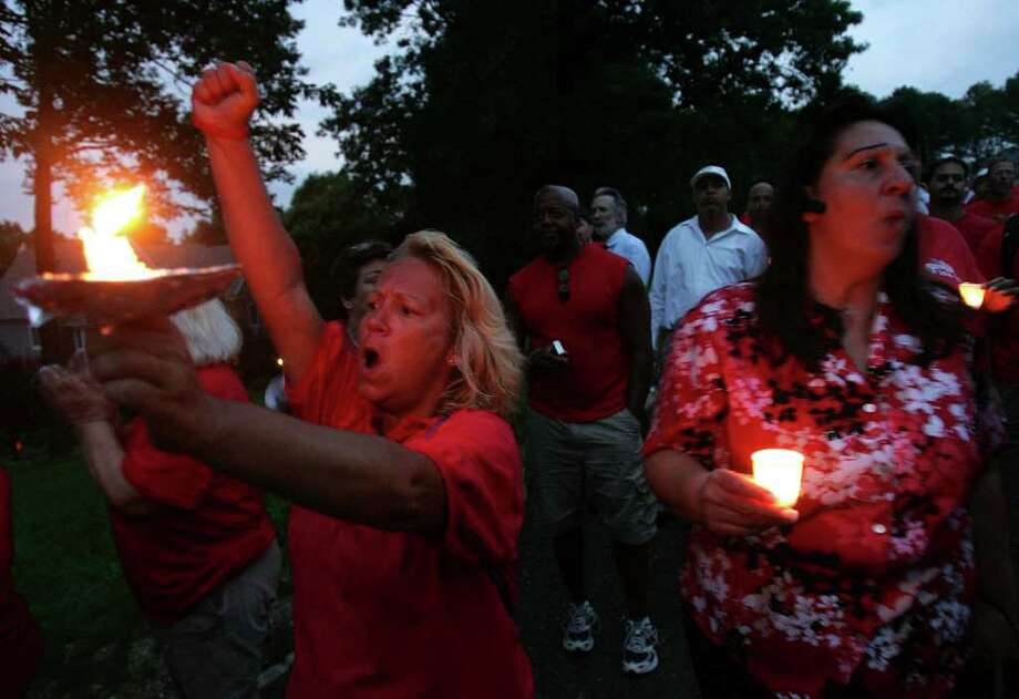 Gail Reed, left, of Runnemede, N.J. and Fran Ehret, right, of Jamesburg, N.J. join other striking Verizon workers picketing and holding a candle light vigil at the home of Verizon CEO Lowell McAdam in Mendham, N.J., Thursday, Aug. 18, 2011. (AP Photo/Rich Schultz) Photo: Rich Schultz
