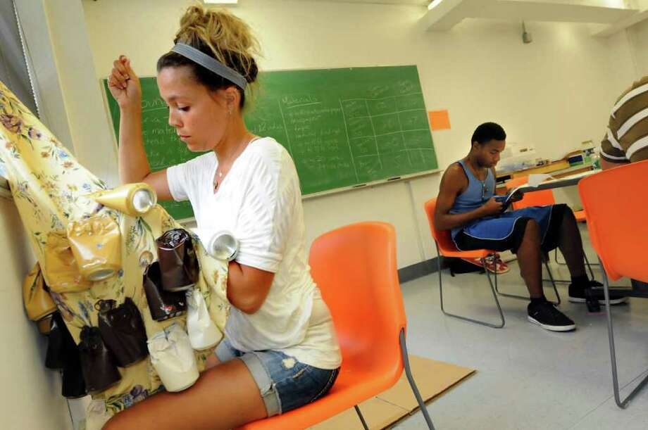 """Graduate student Christine Flood, left, stitches painted soda cans, filled with ingredients like hard pasta, onto a dress that will be part of a """"soundsuit"""" during art camp on Wednesday, Aug. 3, 2011, at the College of Saint Rose in Albany, N.Y. (Cindy Schultz / Times Union) Photo: Cindy Schultz"""