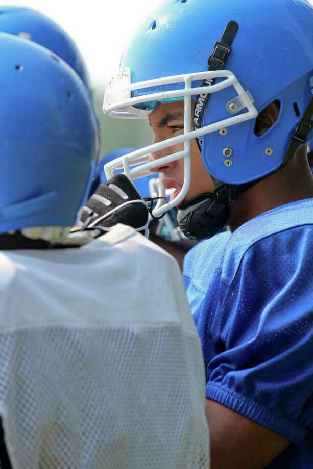 High school football -- Shaker High School football player Adrian Valentino stands in a huddle at a football camp on Friday, Aug. 19, 2011. (Erin Colligan / Special To The Times Union)