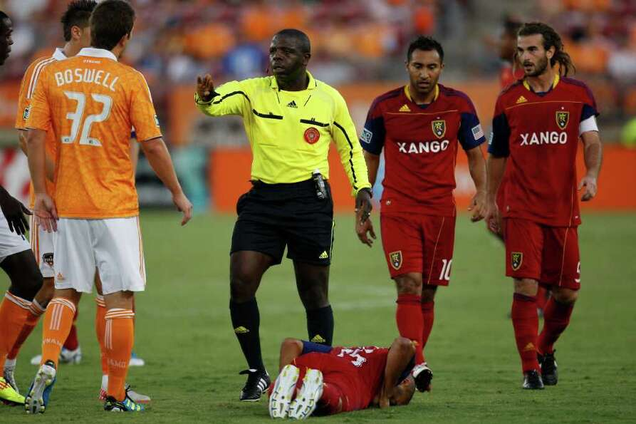 Referee Abiodun Okulaja separates Bobby Boswell (32) from Real Salt Lake's Donny Toia as he lies on