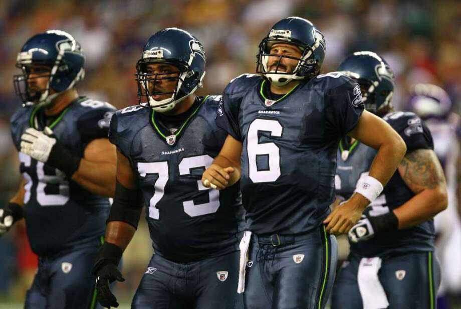 Seahawks quarterback Charlie Whitehurst (6) is helped off the field by teammate William Robinson (73) after Whitehurst took a hit. Photo: JOSHUA TRUJILLO / SEATTLEPI.COM