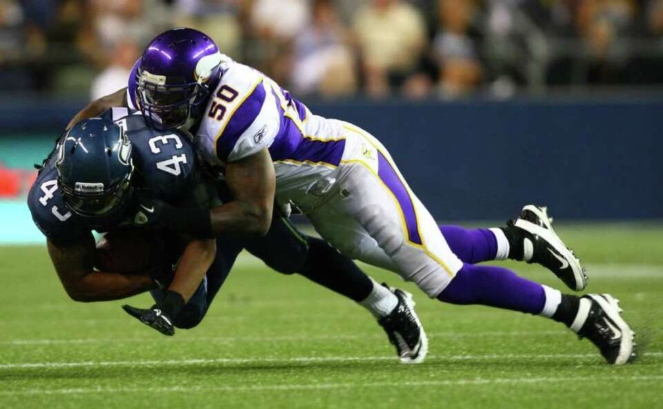 Seahawks player Dorson Boyce (43) is taken down by  Minnesota Vikings player Erin Henderson.