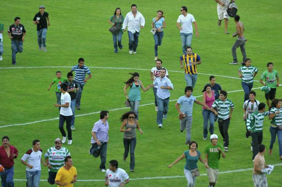 Fans run away from a shootout during a football match between Santos and Morelia, which had to be suspended, at Corona stadium, in Torreon, Coahuila State, Mexico, on August 20, 2011. Photo: STR, Getty Images / 2011 AFP