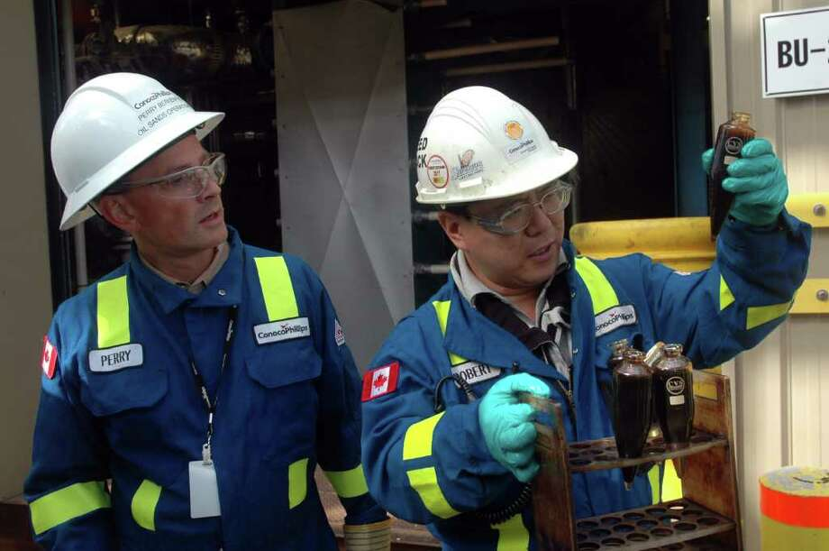 Robert Lee, a lab technician at ConocoPhillips' Surmont oil sands project in Alberta, examines a vial of water and oil sediment. Looking on is Perry Berkenpas, vice president of oil sands operations for ConocoPhillips Canada.