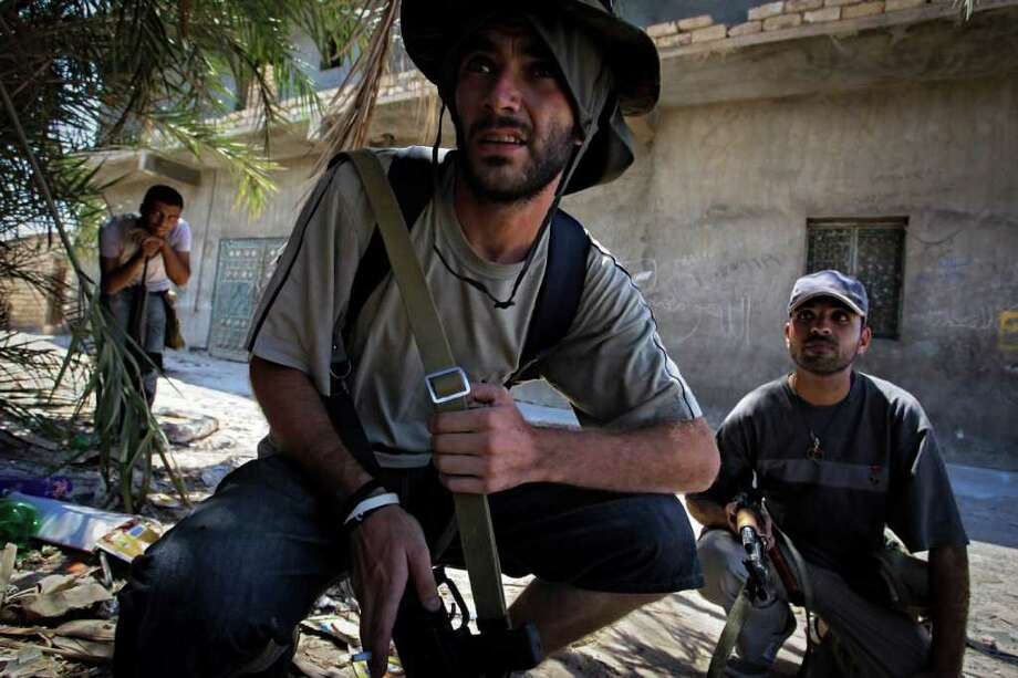 Rebel fighters look towards the enemy as they hear the sound of bombardments in the village of Mayah, some 30 kilometers west from Tripoli, LIbya, Sunday, Aug. 21, 2011.  Libyan rebels said they were less than 20 miles (30 kilometers) from Moammar Gadhafi's main stronghold of Tripoli on Sunday, a day after opposition fighters launched their first attack on the capital itself. Fighters said a 600-strong rebel force that set out from Zawiya has reached the outskirts of the village of Jedaim and was coming under heavy fire from regime forces on the eastern side of the town. (AP Photo/Sergey Ponomarev) Photo: Sergey Ponomarev, STF / AP