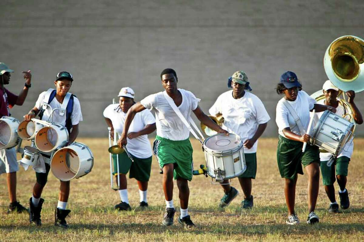 In front row, from left, O.J. Simpson, 16, Antwan James, 17, and Aleshana Toliver, 14, run back to the starting line after marching and playing during a 100-degree evening practice last week at HISD's Worthing High School.