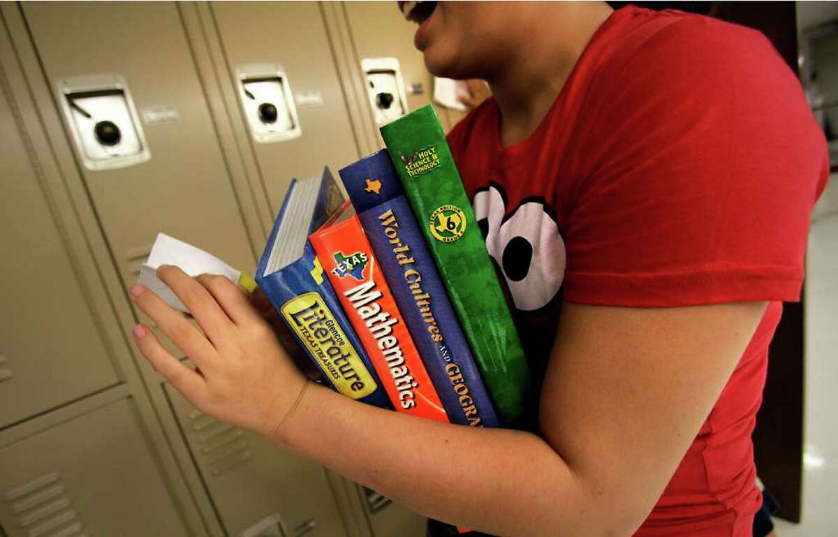 A new student at Eisenhower Middle School prepares to put away her books last week. For some districts, new texts could be delayed for months.