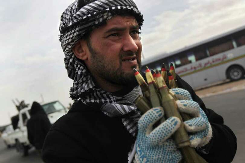 RAS LANUF, LIBYA - MARCH 10:  A Libyan rebel carries anti-aircraft ammunition at a checkpoint on Mar