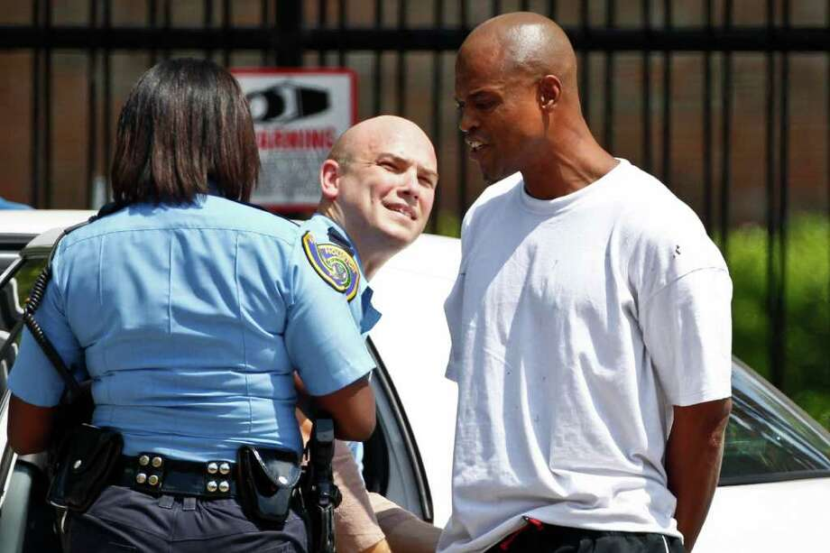 The alleged perpetrator who walked into an office building at 1707 Calumet wearing a backpack and making threats according to an HPD official, is taken into custody after a 2-hour standoff with the SWAT team and HPD officers in the Museum District, Monday, Aug. 22, 2011, in Houston. Photo: Michael Paulsen, Paulsen / © 2011 Houston Chronicle