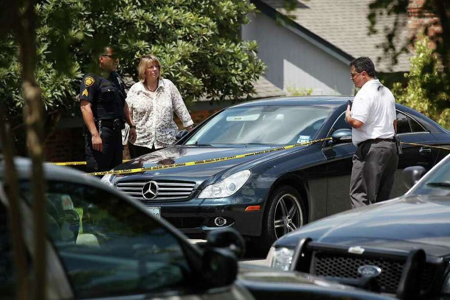 San Antonio Police personnel try to open a car as they investigate the scene of a home burglary shooting. The suspect was shot in the abdomen by a person inside the residence after he broke through the front door. The suspect was transported to University Hospital. Photo: JERRY LARA, San Antonio Express-News / SAN ANTONIO EXPRESS-NEWS