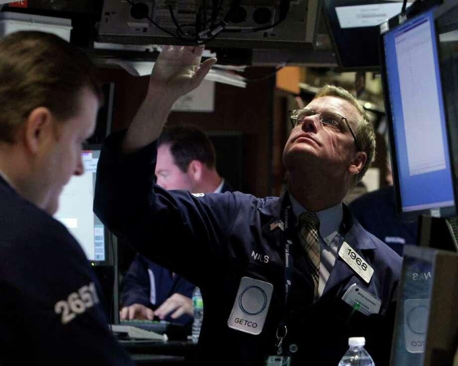 Specialist Nils Petrik works on the floor of the New York Stock Exchange Monday, Aug. 22, 2011. (AP Photo/Richard Drew) Photo: Richard Drew, STF / AP