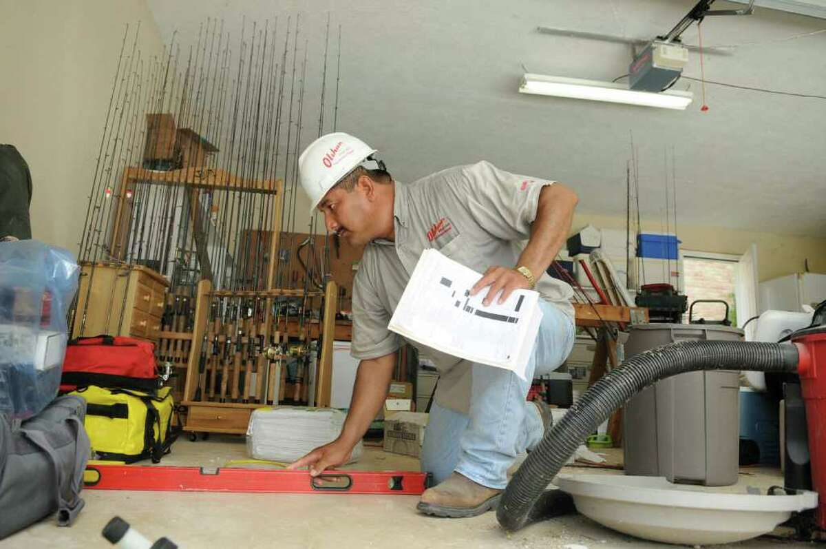 Rodrigo Rosales, of Houston (77086) and a supervisor for Olshan Foundation Solutions, uses a level on the garage floor at the Walden home of Jim and Mary Blacksher during his crew's repairs. Freelance photo by Jerry Baker