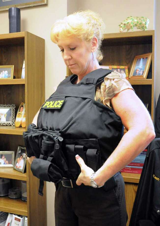 Montgomery County District Attorney Investigator Heather Cash puts on her bullet resistant vest, in her office, before going on an investigation. Cash, a former Montgomery County Sheriiff's deputy, credits her bullet resistant vest with saving her life when her patrol car fell 30 feet off the Peach Creek bridge while responding to a call in 1990. The Montgomery County Sheriff's Department is looking to replace a number of bullet resistance vests using a $70,000 grant. Photo by David Hopper Photo: David Hopper, Freelance / freelance