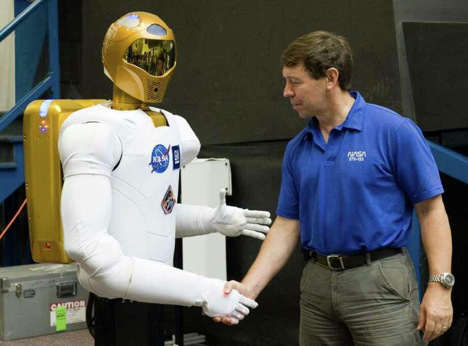 En esta fotografía de archivo del 4 de agosto de 2010 proporcionada por la NASA, el astronauta Michael Barratt saluda al robot humanoide Robonaut 2, también conocido como R2, durante una conferencia de prensa en el Centro Espacial Johnson, en Houston. (Foto AP/NASA, Lauren Harnett, archivo) Photo: Lauren Harnett, HOPD / NASA-JOHNSON SPACE CENTER