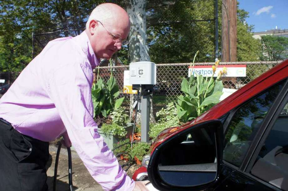 Watson Collins, business development manager for Northeast Utilities, the parent company of Connecticut Light and Power, charges a Chevy Volt electric vehicle at Westport's EV charging station next to Luciano Park on Monday, Aug. 22, 2011. Photo: Paul Schott / Westport News