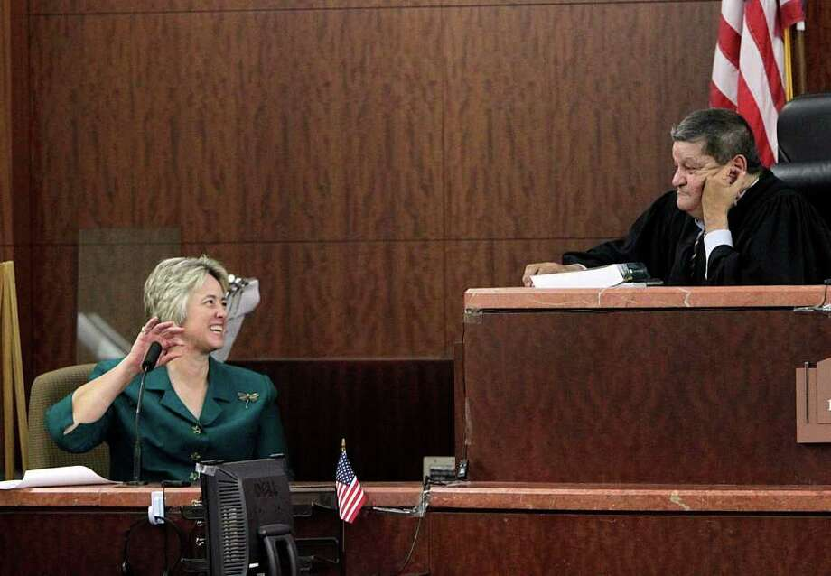 Mayor Annise Parker talks with judge Ruben Guerrero during a change in venue hearing where she said that she believes HPD officers, Andrew Blomberg, Phil Bryan, Raad Hasan and Drew Ryser videotaped beating a teenage burglary suspect will be able to get a fair trial in Houston as she testified in the 174th District Court at the Harris County Criminal Justice Center Monday, Aug. 22, 2011, in Houston.  The video was recorded by a surveillance camera around 4 p.m. March 24, 2010, at Uncle Bob's Self-Storage at 8450 Cook near Beechnut shows Chad Holley, then 15, running away from police before he is clipped by an HPD cruiser. The boy then falls to the ground, rolls on the grass, flips onto his stomach and clamps his hands behind his head as officers appear to attack him forcefully. ( Johnny Hanson / Houston Chronicle ) Photo: Johnny Hanson, Staff / © 2011 Houston Chronicle