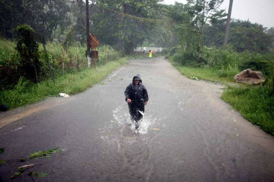 A man wades through a flooded street after hurricane Irene hit the area in Naguabo, Puerto Rico, Monday, Aug. 22, 2011. Hurricane Irene headed out over warm ocean water on a path that could take it to northeastern Dominican Republic and part of Haiti early Tuesday and to the U.S. mainland by the end of the week. (AP Photo/Ricardo Arduengo) Photo: Ricardo Arduengo, STR / AP