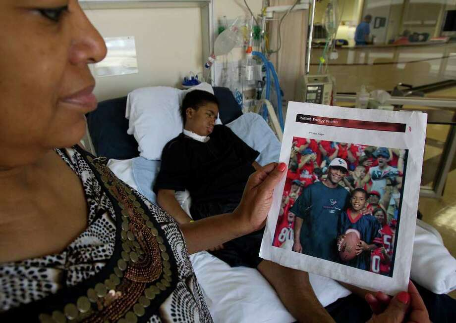 Rosslyn Allen holds a photo of her son Jordan and his father Samuel taken before Jordan was diagnosed with brain cancer as he is seen in the background at Atrium Medical Center Monday, Aug. 22, 2011, in Stafford, Tx. (Cody Duty / Houston Chronicle ) Photo: Cody Duty, Staff / © 2011 Houston Chronicle