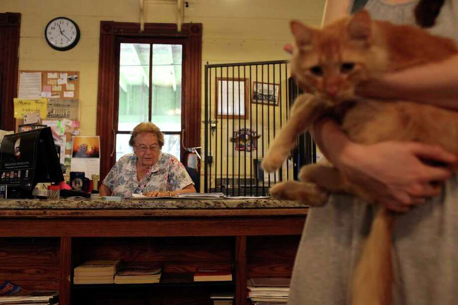 Metro - Postmaster Dorothy Beyer works while customer Hannah Southall holds the community cat, Maggie, at the Hye Post Office in Hye on Thursday, August 18, 2011. The Post Office is located inside Kathy's Corner Antique Mall. LISA KRANTZ/lkrantz@express-news.net Photo: LISA KRANTZ, STAFF / SAN ANTONIO EXPRESS-NEWS