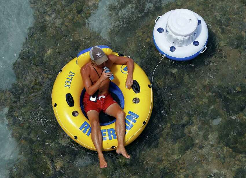 A tuber pulls a cooler along as he floats the Comal River, Monday, Aug. 22, 2011, in New Braunfels, Texas. (AP Photo/Eric Gay)