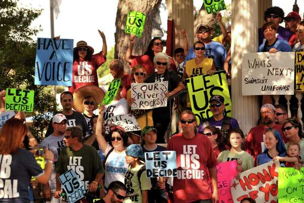 People gather on the New Braunfels Main Plaza to protest a proposed city council ordinance to ban disposable containers on the Comal River.