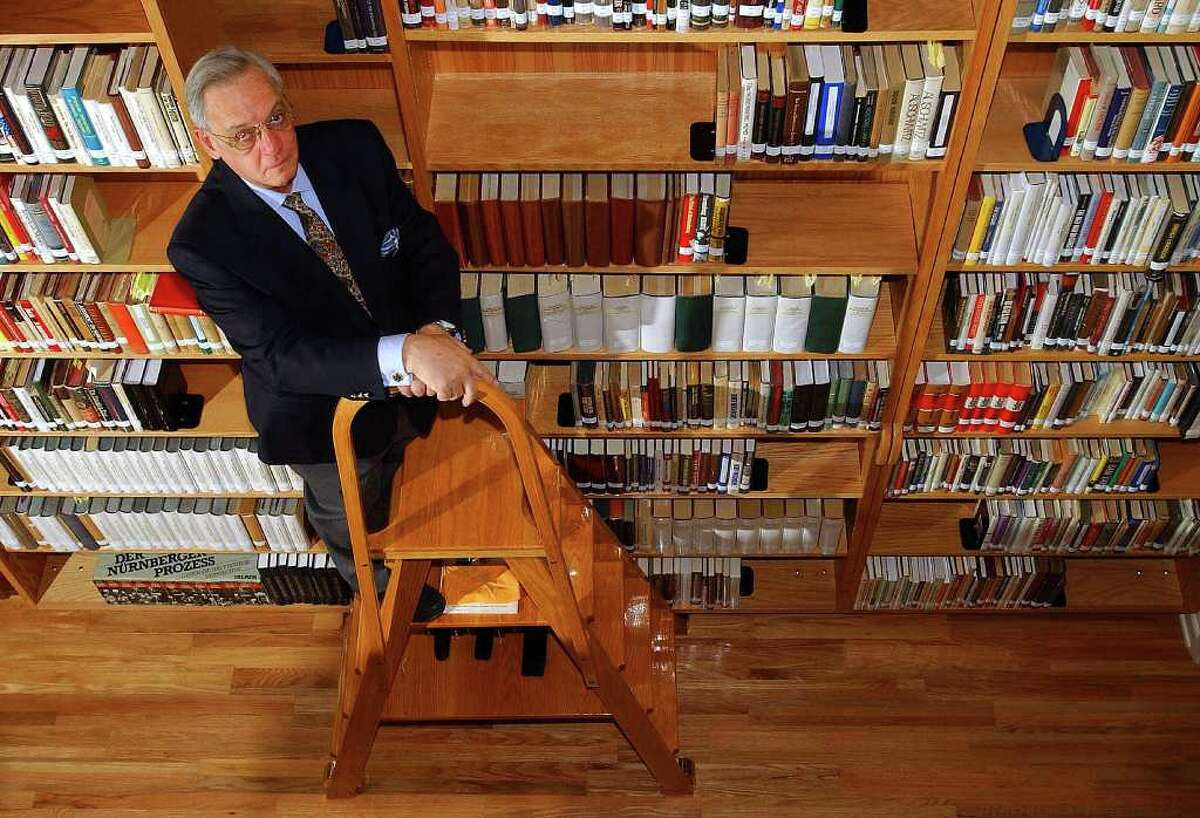 """Harry W. Mazal, posed on a stepladder amid the Mazal Holocaust History Library's books and documents, battled cancer for 15 years. His life's work of discrediting Holocaust deniers """"was his passion,"""" his daughter says. """"It was his heart."""""""