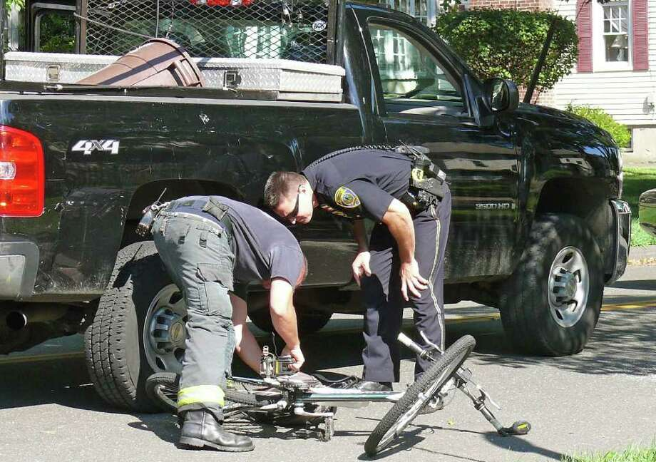 Police and firefighters were on the scene Monday afternoon when a bicyclist was struck by a pickup truck at Paulding Place and Rowland Road. Photo: Genevieve Reilly / Connecticut Post