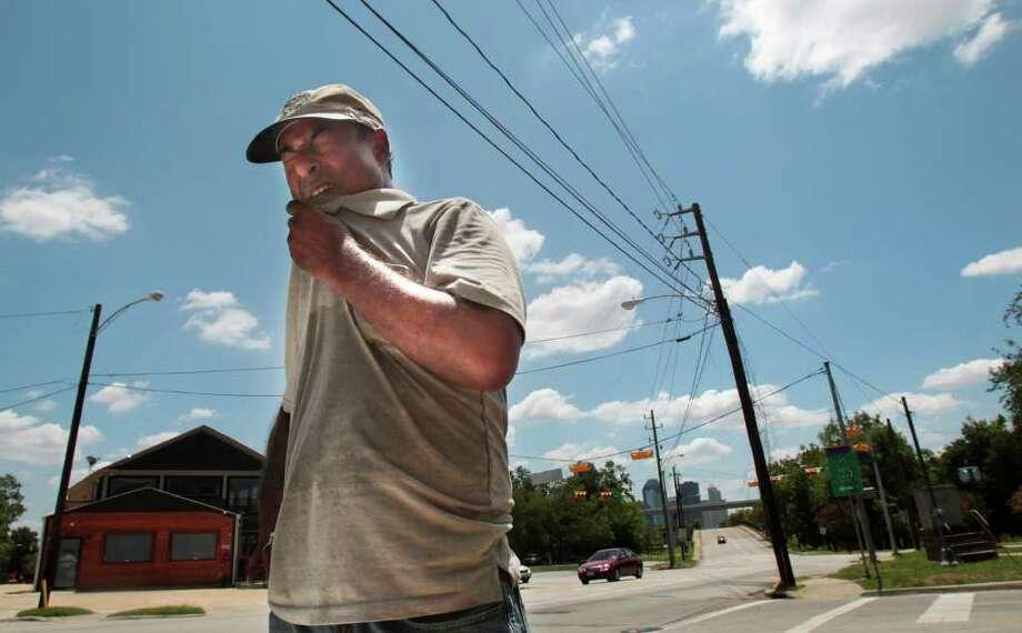 Mohammad Salahuddin, dueño de Elegant Sign, se seca la transpiración mientras trabaja arreglando un letrero en una gasolinera de Houston. ( Cody Duty / Houston Chronicle ) Photo: Cody Duty, Staff / © 2011 Houston Chronicle