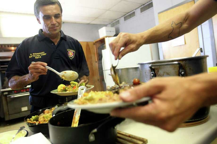 Batallion Chief Ron Rodriguez prepares to sample a firehouse meal at San Antonio Fire Station 43. Photo: Jennifer Whitney, Special To The Express-News / special to the Express-News