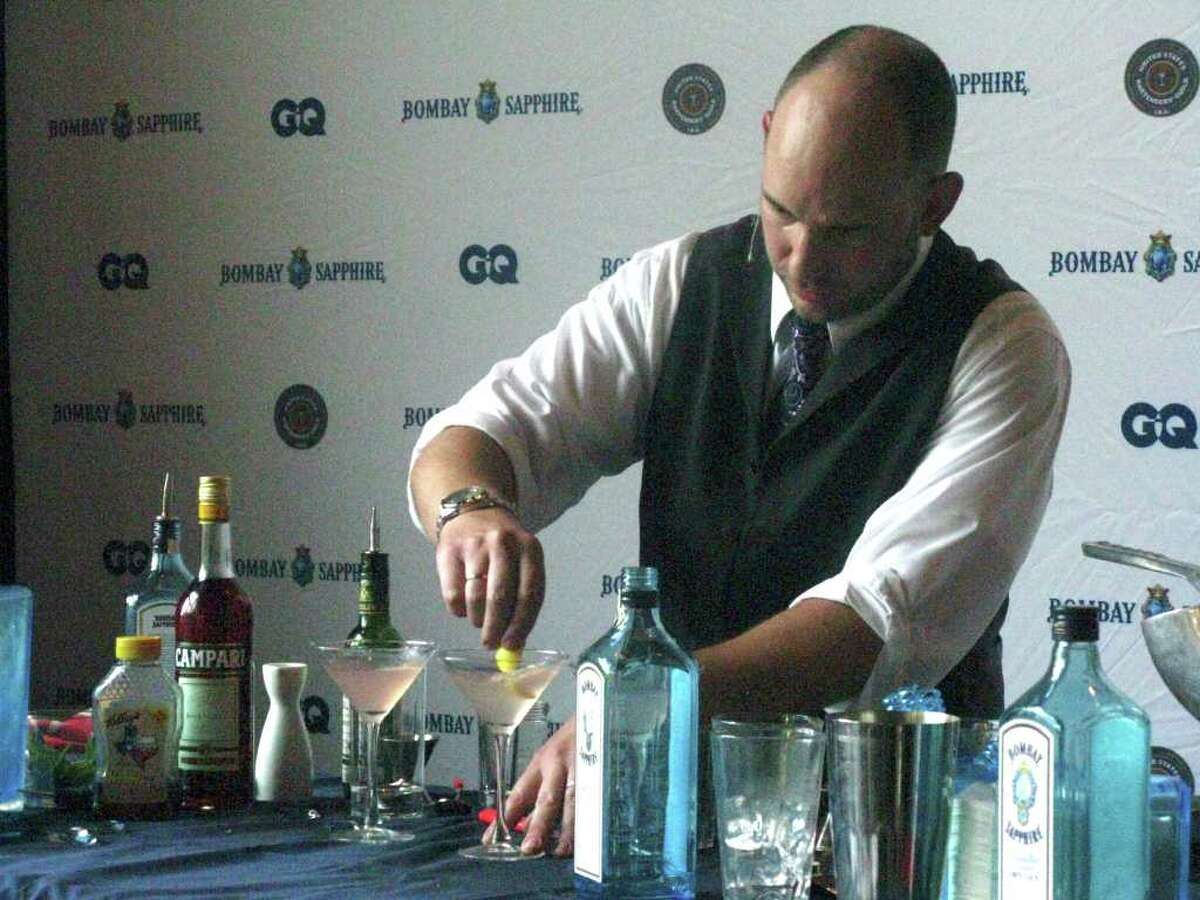 Olaf Harmel, bar man at Mon Ami, puts a lemon zest curl in his Salmonesque cocktail for the Bombay Sapphire Most Inspired Bartender competition at Malverde in Austin.