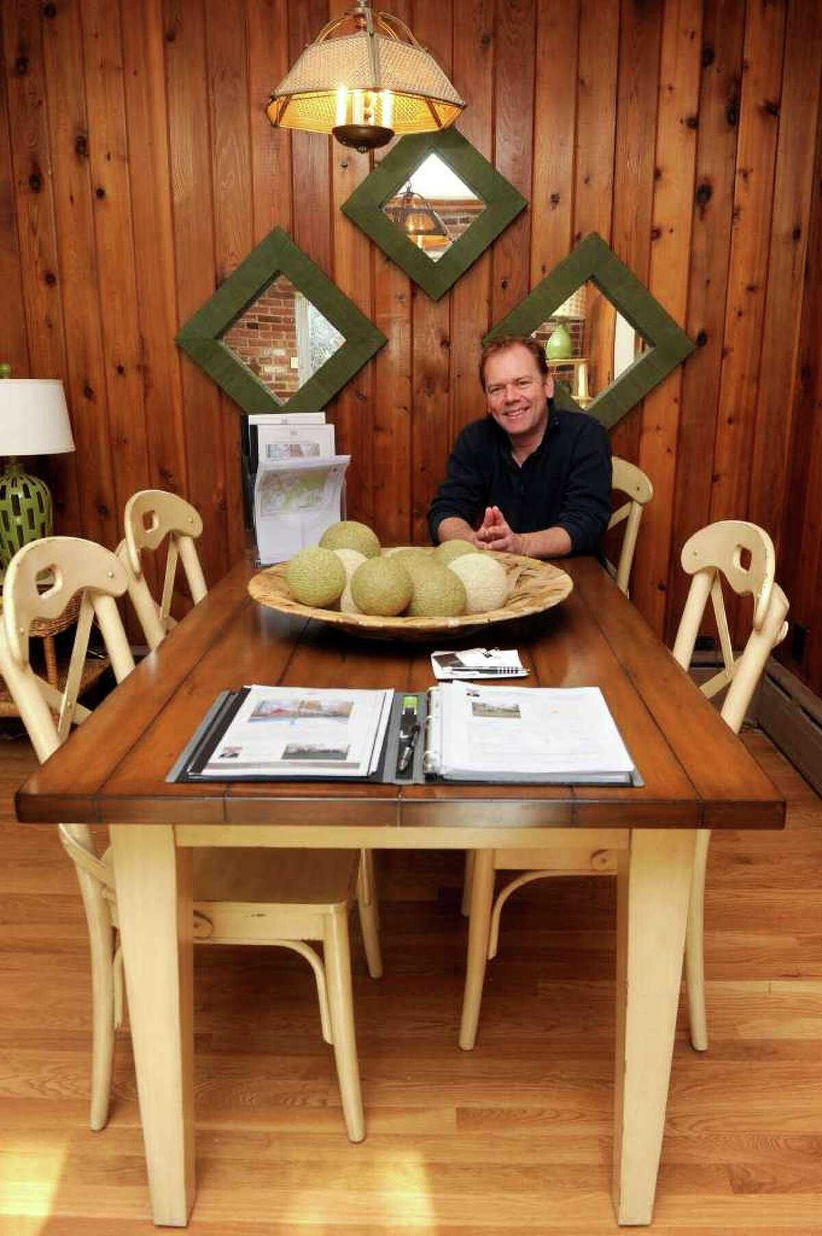 George Knapp, property manager at 4 Lehn Farm Rd in Westport, poses for a photo in the house, which is for sale. On the table is sale paperwork and information for potential buyers.