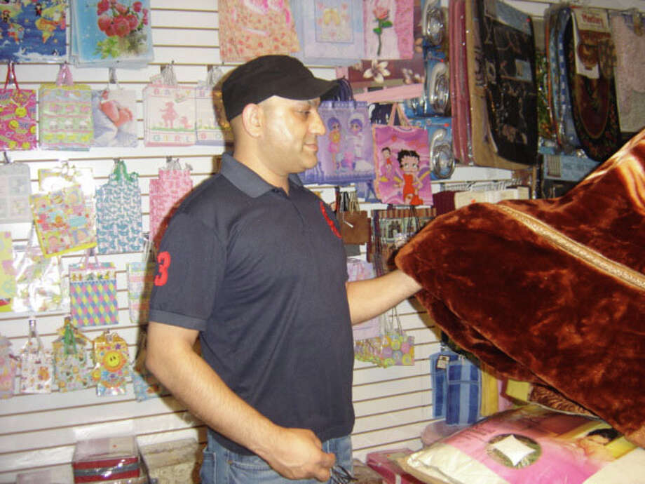 Owner Ajaz Shaikh shows the plush fabric in a blanket he sells at his store, Dollar Plus, at 68 Lake Ave. in Danbury. The blanket was on sale that day for $49.99 though 80-percent of the store's inventory sells for 99 cents or $1. Photo: Carol Kaliff