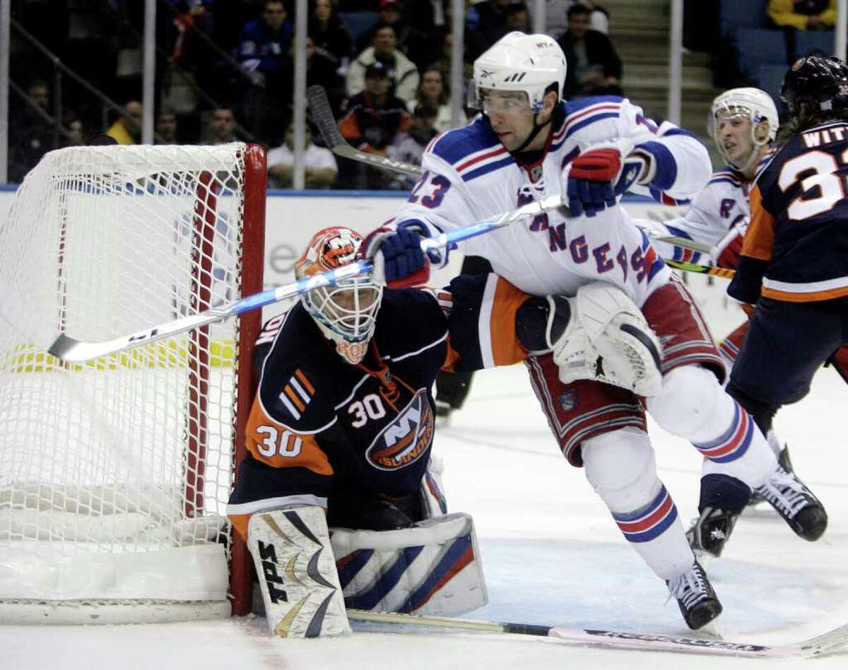 New York Islanders goalie Dwayne Roloson, left, keeps an arm on New York Rangers' Chris Drury during the third period of the NHL hockey game Wednesday, Oct. 28, 2009, in Uniondale, N.Y. The Islanders beat the Rangers, 3-1.