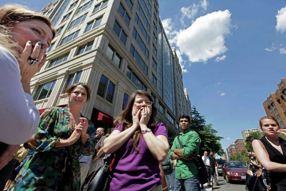 Office workers gather on the sidewalk in downtown Washington, Tuesday, Aug. 23, 2011, moments after a 5.9 magnitude tremor shook the nation's capitol. The earthquake centered northwest of Richmond, Va., shook much of Washington, D.C., and was felt as far north as Rhode Island and New York City.  (AP Photo/J. Scott Applewhite) Photo: J. Scott Applewhite, STF / AP