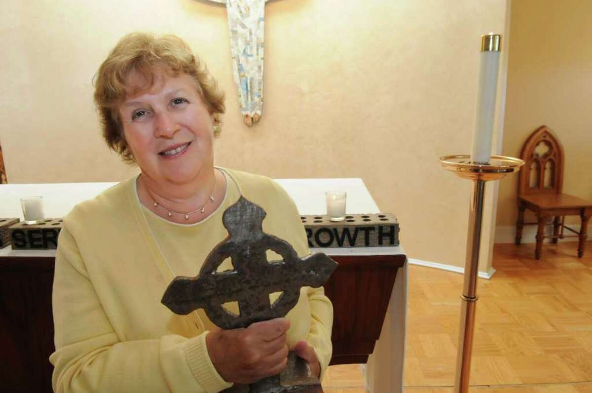 Jayne Collins, a history teacher and head of the Upper School at Convent of the Sacred Heart in Greenwich since the week of Sept. 11, 2001, stands in the school's chapel on Tuesday, Aug. 23, 2011, holding a cross made from World Trade Center steel that was given to the school.