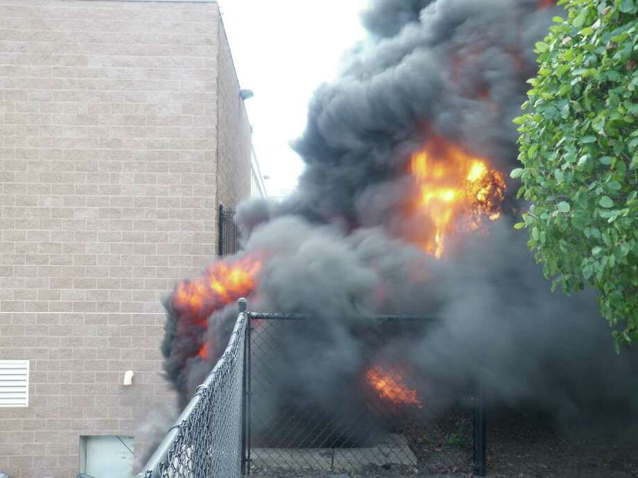 Flames erupted from old computers piled next Bedford Middle School's loading dock Tuesday afternoon, licking the side of the structure before firefighters extinguished the blaze. Photo: Westport Fire Department / Westport News contributed