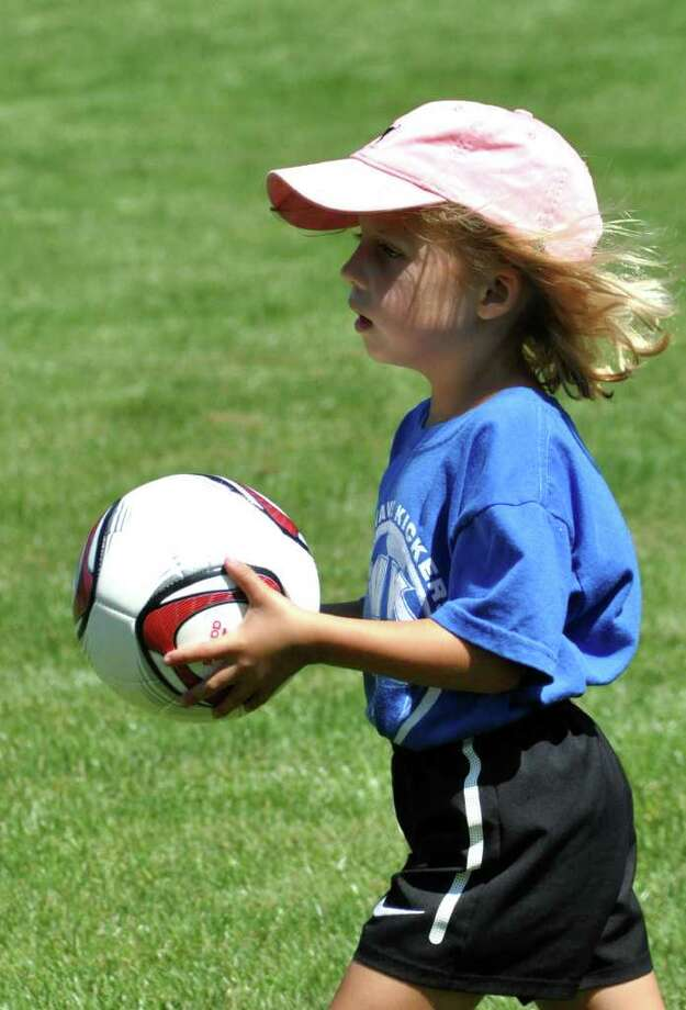 Anya Anderson, 4, of Stamford, carries her soccer ball during practice at the NOGA soccer camp held at Darien Town Hall on Renshaw Road on Tuesday, Aug. 23, 2011. Photo: Amy Mortensen / Connecticut Post Freelance