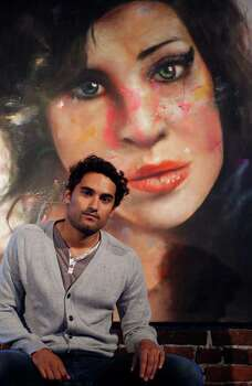 Artist Johan Andersson poses alongside his painting of British singer Amy Winehouse at the Lock Tavern in London's Camden Town,Tuesday, Aug., 23, 2011. The painting will be exhibited in the London Underground station at Camden Town, the area where Winehouse, who died earlier this year at the age of 27, was best know for her escapades. Andersson's work has previopusly been displayed in other major London Underground stations including Bond Street, Baker Street and South Kensington.(AP Photo/Alastair Grant) Photo: Alastair Grant / AP