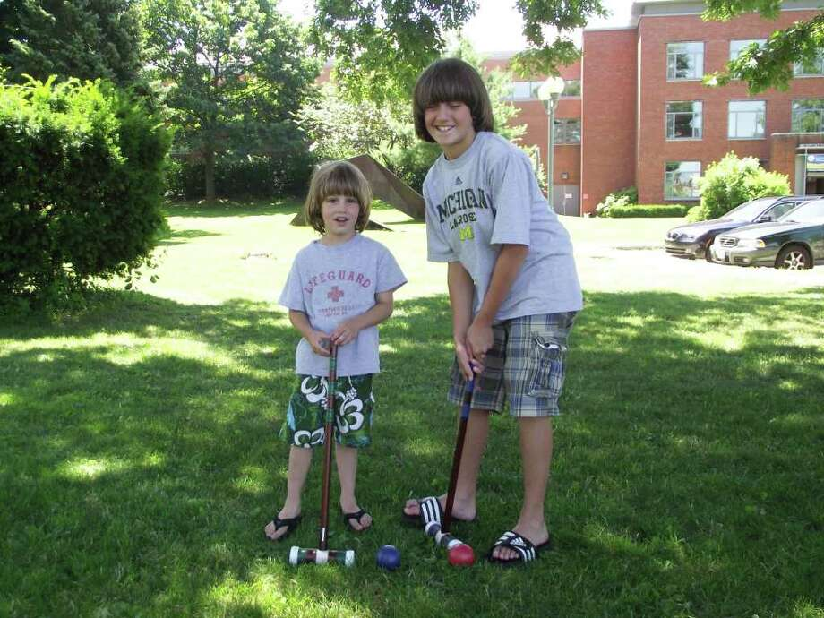 The Westport Public Library is now allowing patrons to check out bocce, badminton and croquet sets for use on Jesup Green, which is adjacent to the library. In this photo, five-year-old Cisco Celotto and 10-year-old Skyler Celotto hold two of the croquet mallets for demonstrative purposes. Photo: Contributed Photo