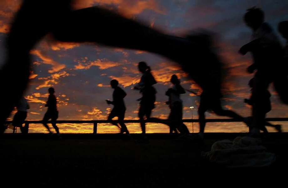 01.15.06 - Marathon participants view the sunrise while they run out of downtown Houston via the Elysian overpass during the Chevron Houston Marathon. Photo: Mayra Beltran / Houston Chronicle / Houston Chronicle
