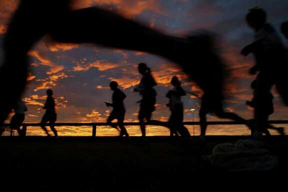 01.15.06 - Marathon participants view the sunrise while they run out of downtown Houston via the Elysian overpass during the Chevron Houston Marathon.