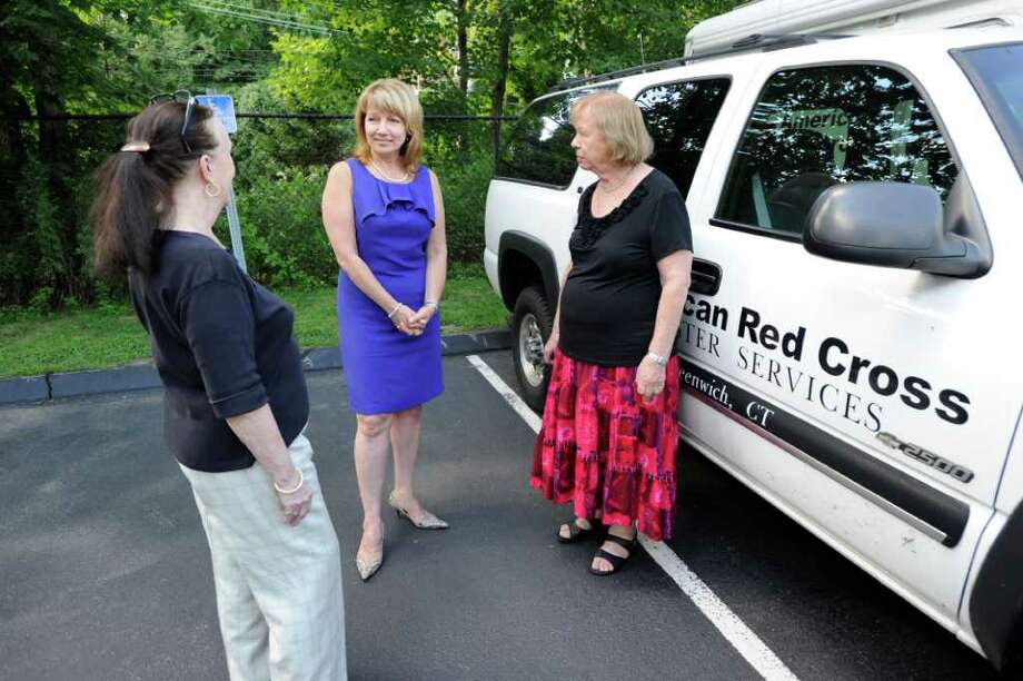 American Red Cross workers, Barbara DeGaetani, left, and Esme Ingledew, right, speak with American Red Cross chief executive officer for the Greenwich chapter, Mary Young, at Greenwich Chapter headquarters at 99 Indian Field Road, Tuesday afternoon, Aug. 23, 2011. The American Red Cross has announced that its Greenwich and Westchester County chapters, as well as operations in Orange, Putnam, Rockland and Sullivan counties, will consolidate into a new regional chapter based in Greenwich. Photo: Bob Luckey / Greenwich Time