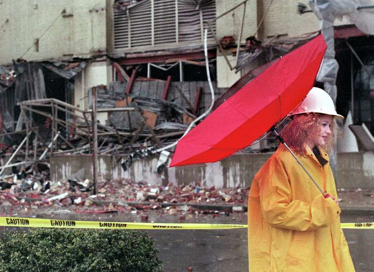 Amy Castner of Seattle works security during a windy down pour of rain at the earthquake-damaged Sodo building in Seattle on March 1, 2001, a day after the Nisqually quake.