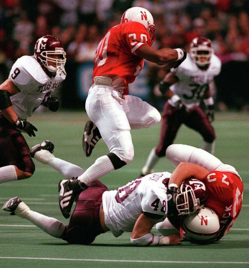 Nebraska's Ahman Green hurdles over teammate Fred Pollack and Texas A&M's Rich Coady, as the Aggies' Dat Nguyen closes in for the tackle during the 1997 Big 12 Championship at the Alamodome. Nebraska won 54-15. Photo: Kin Man Hui/kmhui@express-news.net