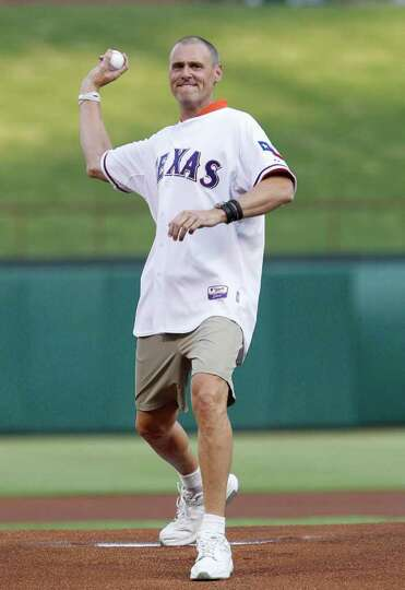 Dallas Mavericks head coach Rick Carlisle throws out the first pitch for the baseball game between t