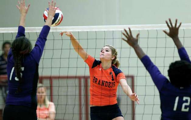 Brandeis' Chelsea McCloud tries to punch the ball during Warren's victory on Tuesday, Aug. 23, 2011 at O'Connor Gym. The victory was the Warriors' first in district play against the Broncos in seven tries. Photo: Tom Reel/treel@express-news.net / © 2011 San Antonio Express-News