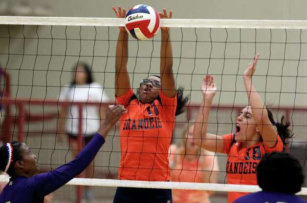 Brandeis' Taylor Mastin (13) gets up to block a shot by Warren's Jasmine Richardson while teammate Alex Parker (18) moves in during the Warriors' victory on Tuesday, Aug. 23, 2011 at O'Connor Gym. The victory was Warren's first in district play against the Broncos in seven tries. Photo: Tom Reel/treel@express-news.net / © 2011 San Antonio Express-News