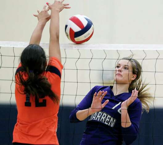 Warren's Shelby Aelvoet waits for the ball to roll off the net as Brandeis' Cassidy Acord plays defense during the Warriors' victory on Tuesday, Aug. 23, 2011 at O'Connor Gym. The victory was Warren's first in district play against the Broncos in seven tries. Photo: Tom Reel/treel@express-news.net / © 2011 San Antonio Express-News
